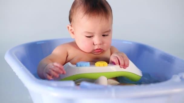 Malý chlapec hraje a koupání ve vaně děti modré