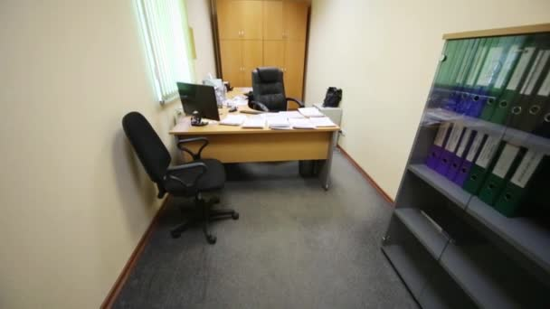 A small office with spacious work desk and soft armchairs
