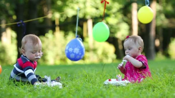 Dvě obarvená miminka jedí koláče se svíčkami ve tvaru 1