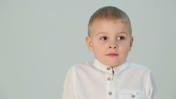 Malý chlapec v bílé košili, stojící vedle šedá zeď