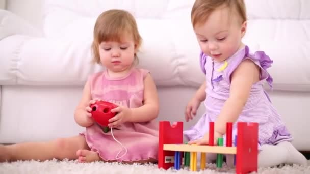 Two kids play with toy for development of thinking on carpet