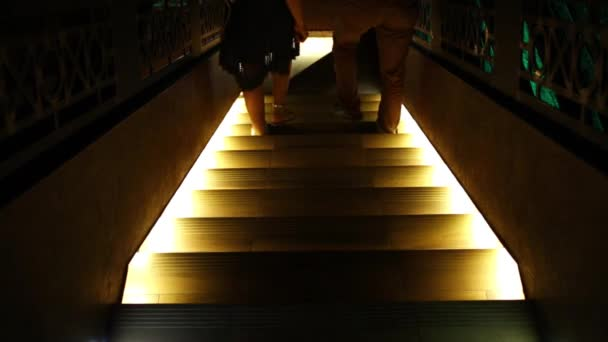 Legs of two people who go down the stairs, lit from below.