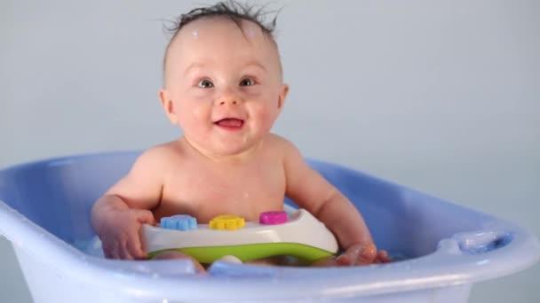Holčička s mokrými vlasy sedí ve vaně modré dětské