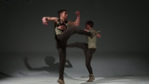 Two young dancers in medieval hunting costume jump in studio