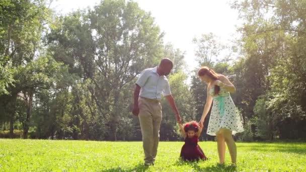 Šťastní rodiče procházky se svou malou dcerou v parku