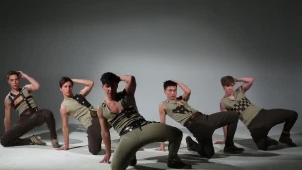 Five handsome men in medieval costumes dance in studio