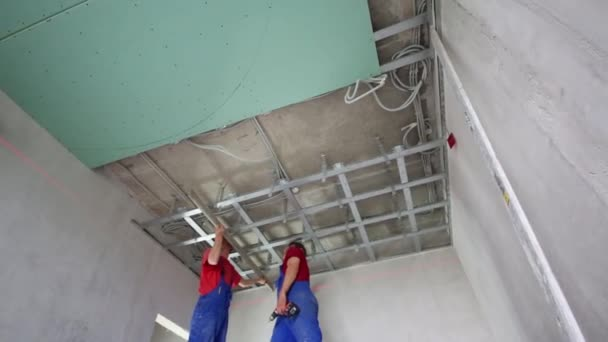 Workers verify accuracy of installation frame for hung ceiling
