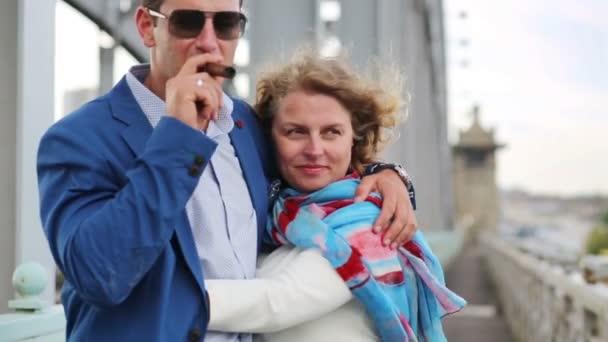 Frau umarmt Zigarre rauchenden Mann und streicht ihm auf Brücke über die Wange