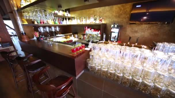 Bar counter with empty beer mugs, beverages in bottles
