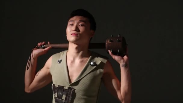 Handsome asian man in medieval costume stands with mace in studio