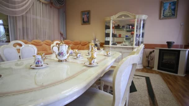 Table with set of porcelain dishes in empty light room