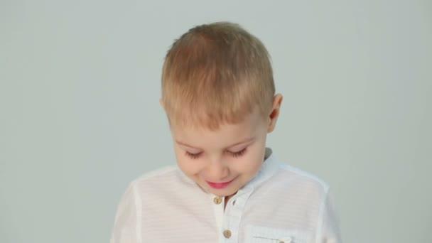 S úsměvem malého chlapce v bílé košili, stojící vedle šedá zeď