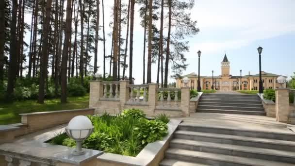 Velký krásný zámek s věží a schodiště v parku na léto