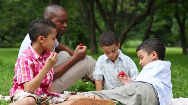 Father and three sons are sitting in park and eating strawberries