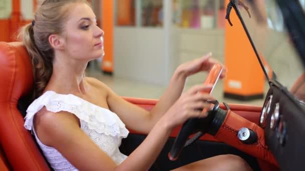 junges schönes Mädchen sitzt am Steuer des Autos
