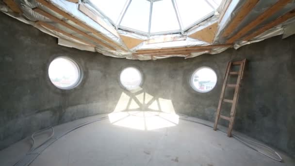 Room with round windows without finishing in two-storey house