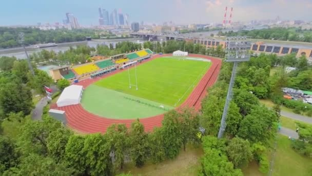 Stadium for rugby against megalopolis with traffic on bridge
