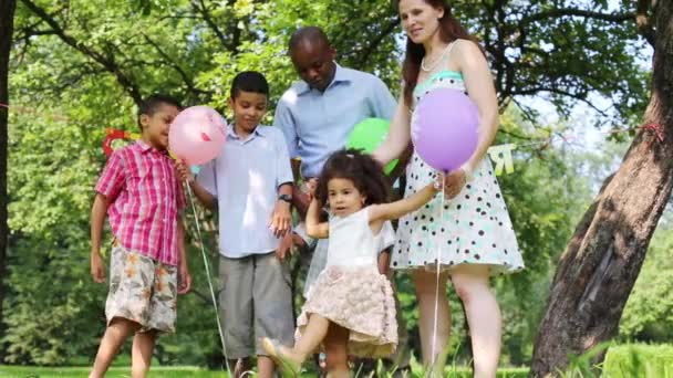 family celebrating a birthday party in the park, children playing