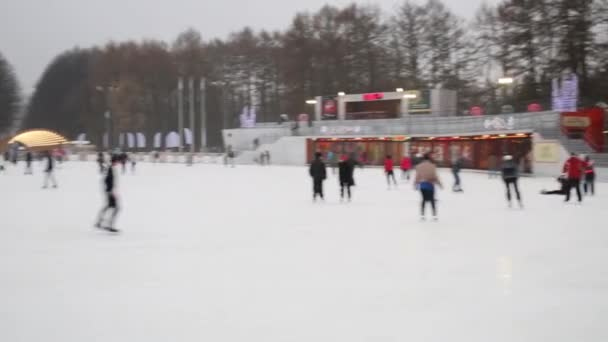 People skate on rink at cloudy winter day in Sokolniki.