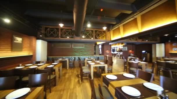 Přehled o sál restaurace s dřevěným nábytkem.
