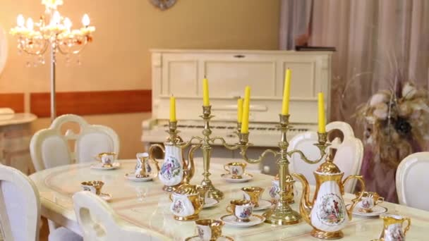Table with set of porcelain dishes and candles and piano