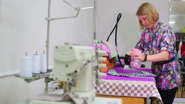 female tailor irons new striped t-shirt near sewing machine