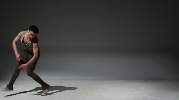 Asian acrobat man in medieval costume graceful jumps in studio