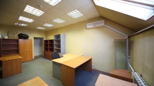 Prostorná kancelář místnost se spoustou prázdné knihovny a pracovní stoly