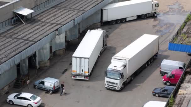 Auto trucks in the courtyard of trading estate, view from roof.