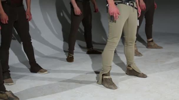 Legs of five men in hunting costumes dancing in grey studio