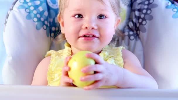 Holčička jí velké zelené jablko, sedět na židličce.