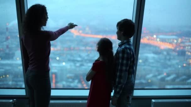 Mother shows children evening cityscape