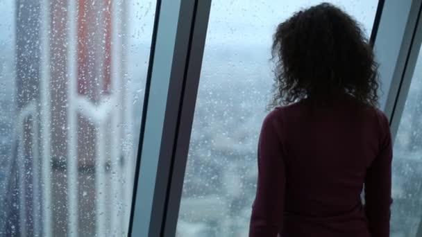 Zadní strana štíhlá žena při pohledu do okna