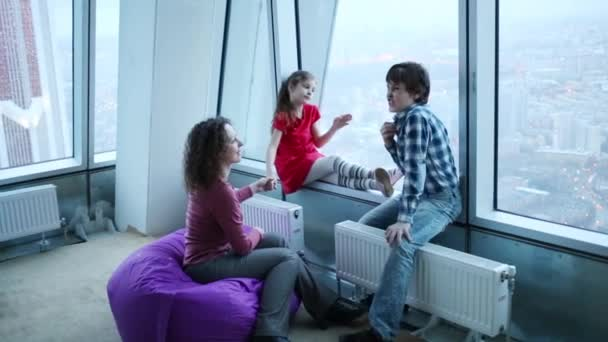 Woman and children sit next to window