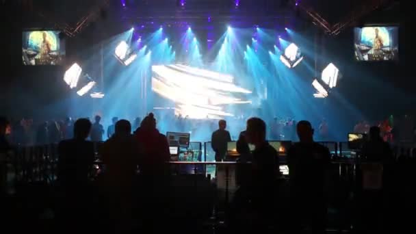 People and stage with DJ performs