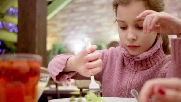 malá dívka sedí u stolu v kavárně