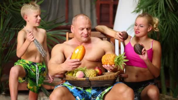 Family near bungalow with fruits.