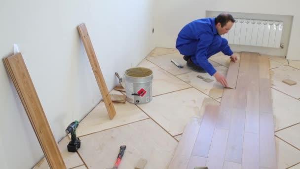 Muž v pracovní oděvy klade podlahy