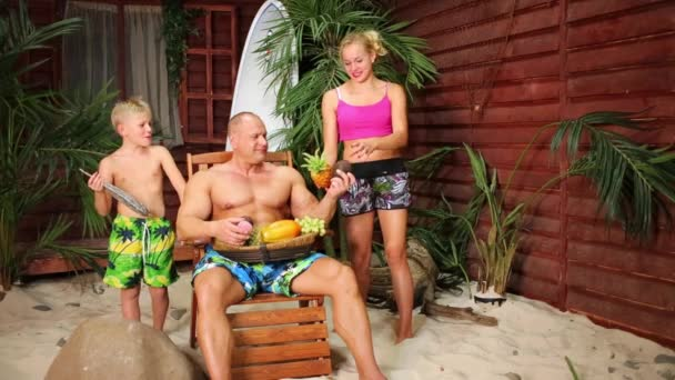 Family on beach near bungalow with fruits