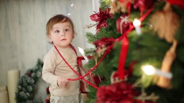Kleines Mädchen steht neben Weihnachtsbaum