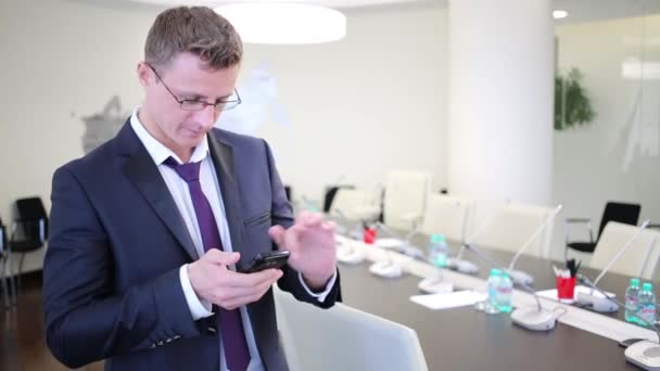 Businessman stands at meeting room with smartphone.