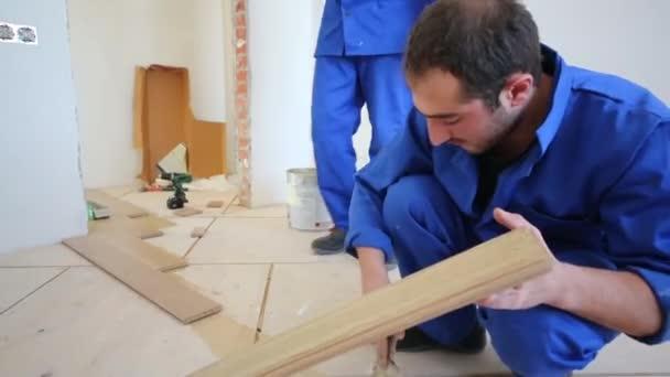 Worker smearing glue on floor