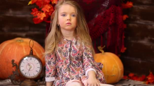 Malá dívka sedí v místnosti s dýní