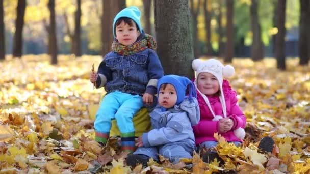 Három gyermek ül a fa közelében