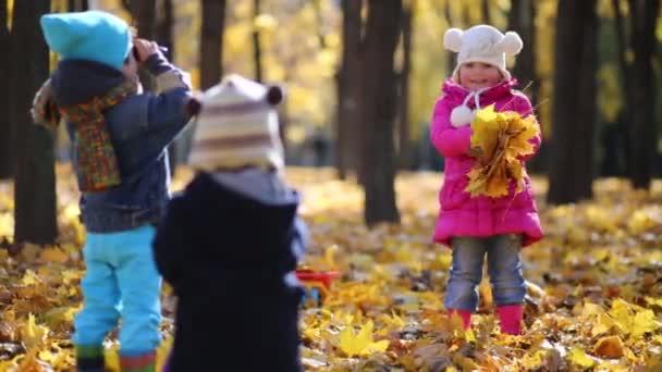Three children play in autumn park