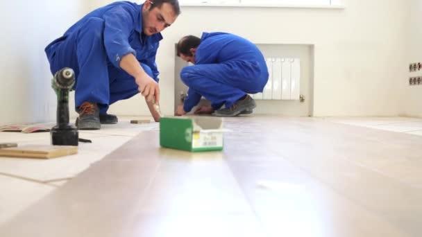 Dělníci instalovat podlahy v novém bytě