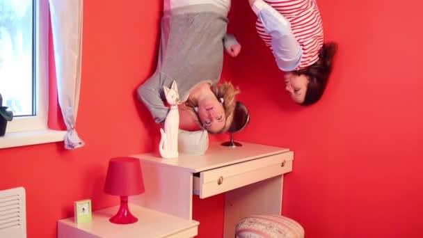 Dvě ženy vzhůru nohama v ložnici