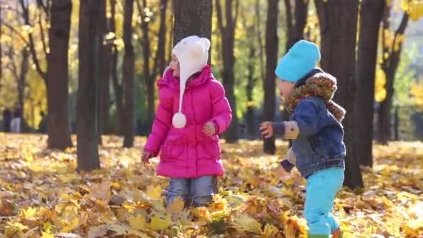 Kinder in der Nähe von Baum im Herbst