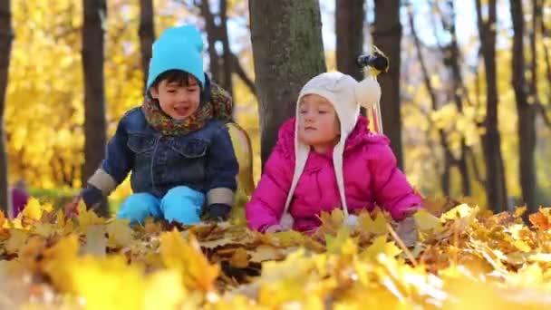 Zwei Kinder sitzen neben Baum