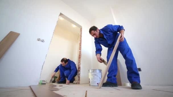 Dva pracovníci instalovat podlahové